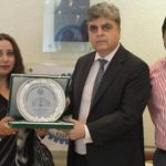 Haroon Agar, President KCCI presenting Crest to Ms. Saira Aslam, Sterling Currency Exchange Ltd.UK Mr. Imran Khanis also seen in the picture.